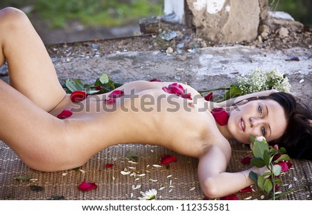 Nude girl with roses. Naked young woman with flowers. - stock photo
