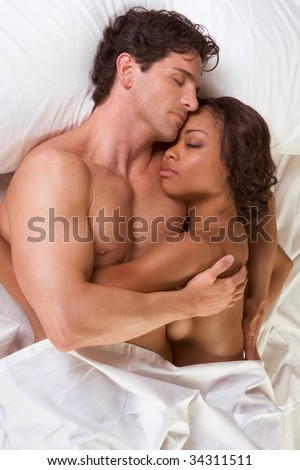nude heterosexual couple in bed peacefully sleeping in embracing each other in hug. Mid adult Caucasian men in late 30s and young black African-American woman in 20s - stock photo