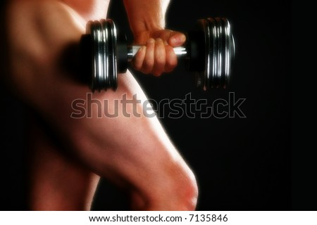 Nude male model with dumbbell over black.