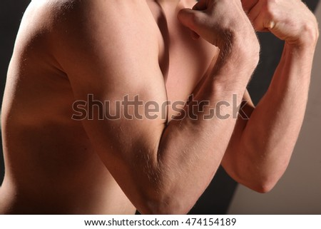 nude male torso and muscle on black background