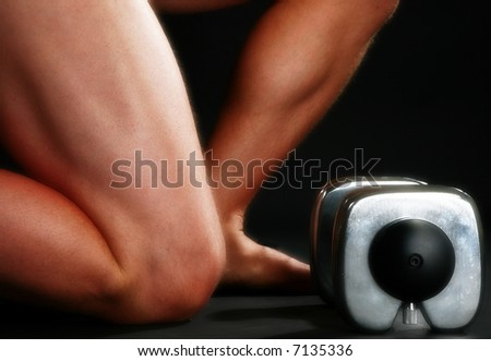 Nude man's legs with dumbell over black.