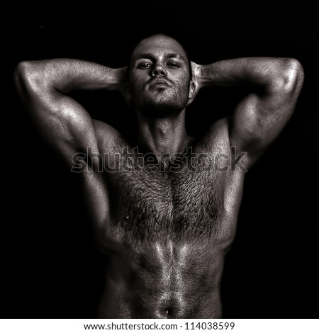 Nude muscular guy posing with hands behind head. Black and white - stock photo
