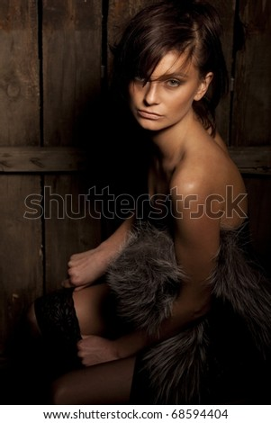 Nude portrait of sexy girl posing on dark wood background