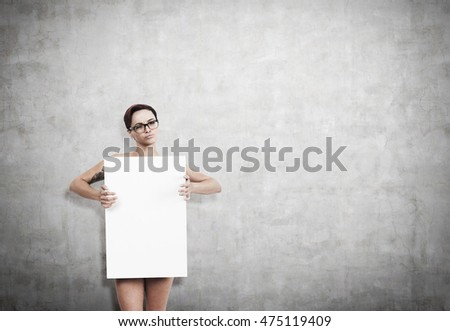 Nude sexy girl wearing glasses holding vertical poster and standing near gray concrete wall. Concept of marketing and advertising. Mockup