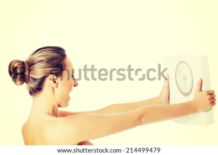 Nude topless woman holding scale. Isolated on white. - stock photo