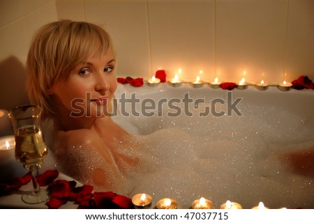 nude woman in foamy bath with petals of roses and by light of candles