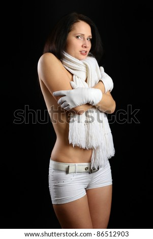 Nude woman is feeling cold and embracing herself. She is wearing a warm scarf on the neck, shorts and gloves. - stock photo