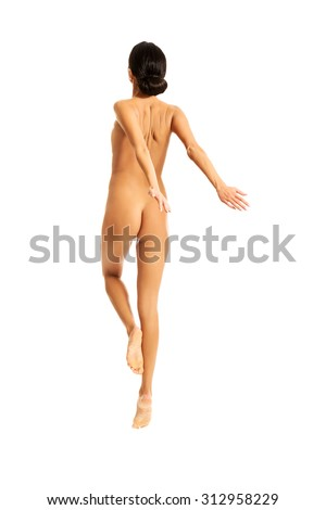 Nude woman jumping with her arms open. - stock photo