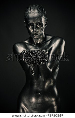 Nude woman like statue in liquid metal holding chains. Selective focus on chains
