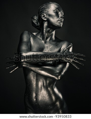 Nude woman like statue in liquid metal posing