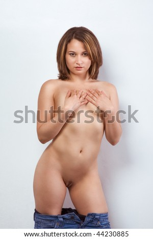 Nude woman of Puerto Rican Ethnicity standing by wall, taking down her pants and covering her boobs - stock photo