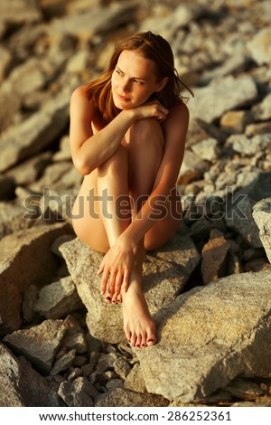 Nude woman on the stone - stock photo