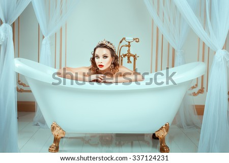 Nude woman sitting in expensive jewelry bath. Crown on his head, his face bright trendy makeup. - stock photo