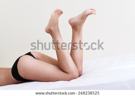 Nude woman with beautiful legs lying on bed - stock photo