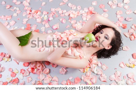 nude woman with roses eating a green apple