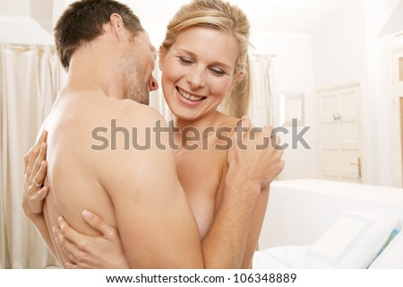 Nude young couple being playful in bedroom.