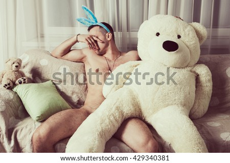 Nude young man sits on the couch in embracing with a big one beige teddy bear, closing his face by the hand and turning away from teddy bear as if they had a fight with each other - stock photo