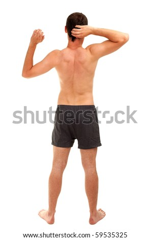 nude young man standing, yawning and stretching, isolated - stock photo