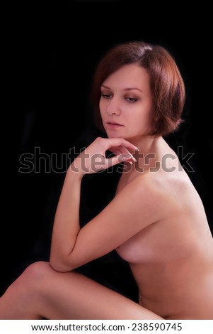 Nude young woman on a black background