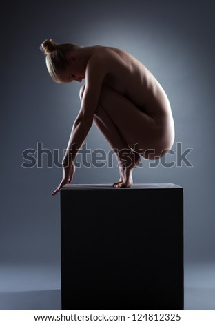 nude young woman posing on cube in dark - stock photo