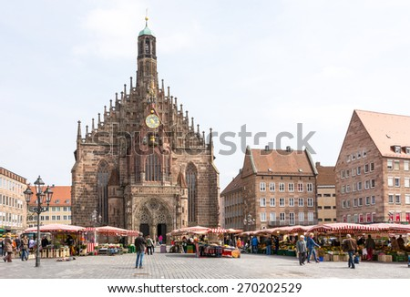 NUERNBERG, GERMANY - APRIL 9: Tourist at the Frauenkirche in Nuernberg, Germany on April 9, 2015. The church is a brick gothic architecture built in the 14th century. Foto taken from Hauptmarkt. - stock photo