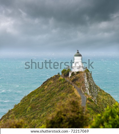 Nugget Point Light House an dark clouds in the sky, Catlins, New Zealand - stock photo