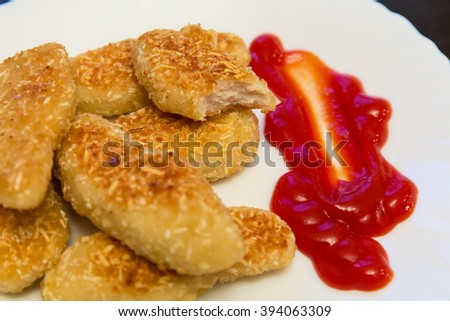 nuggets, breaded in a potato on a white plate - stock photo