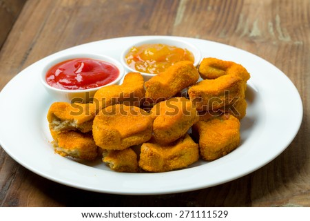Nuggets on a plate with ketchup and sauce
