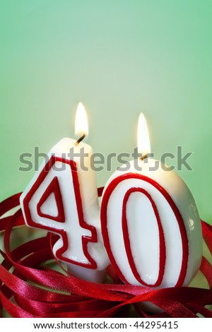 Number 40 candles, surrounded by red ribbon.  40th birthday or anniversary. - stock photo