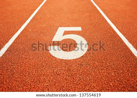 Number five on athletics all weather running track - stock photo