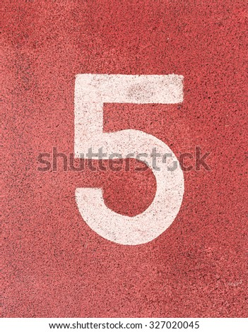 Number five,White track number on rubber racetrack, texture of running racetracks in small stadium. - stock photo