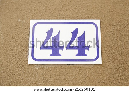 Number forty-four on the wall of a house, detail of a number of information, even number - stock photo