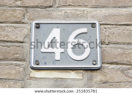 Number forty-six on the wall of a house, detail of a number of information, even number - stock photo