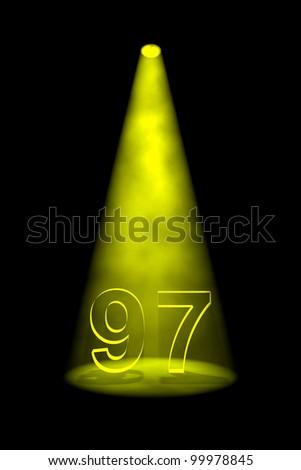 Number 97 illuminated with yellow spotlight on black background - stock photo