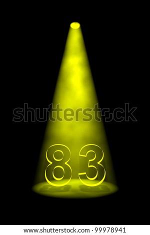 Number 83 illuminated with yellow spotlight on black background - stock photo
