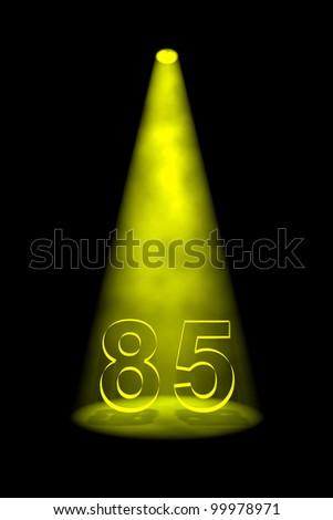 Number 85 illuminated with yellow spotlight on black background - stock photo