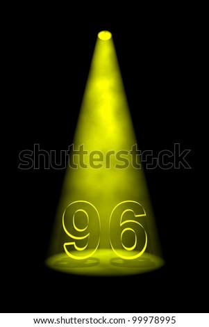 Number 96 illuminated with yellow spotlight on black background - stock photo
