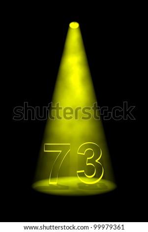 Number 73 illuminated with yellow spotlight on black background - stock photo