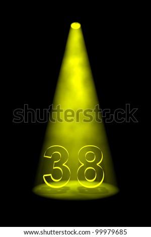 Number 38 illuminated with yellow spotlight on black background - stock photo