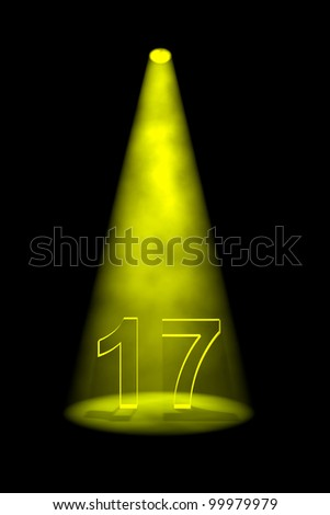 Number 17 illuminated with yellow spotlight on black background - stock photo