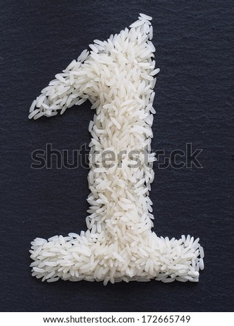 Number 1 made of rice on a black slate - stock photo