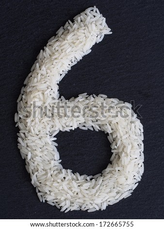 Number 6 made of rice on a black slate - stock photo