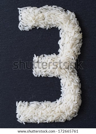 Number 3 made of rice on a black slate - stock photo