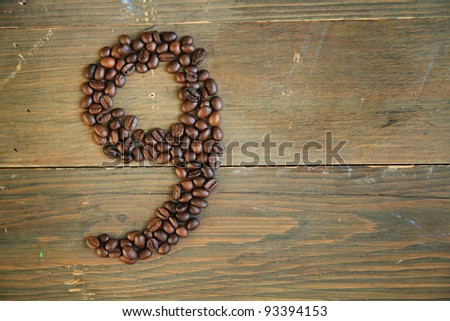 Number nine made with coffee beans on a wooden plank - stock photo
