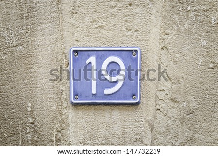 Number nineteen, detail of a metal plate with the number deiecinueve, citrate and text, signal - stock photo