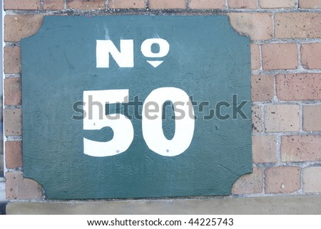 Number 50 on placard on brick wall.  Horizontally framed shot. - stock photo