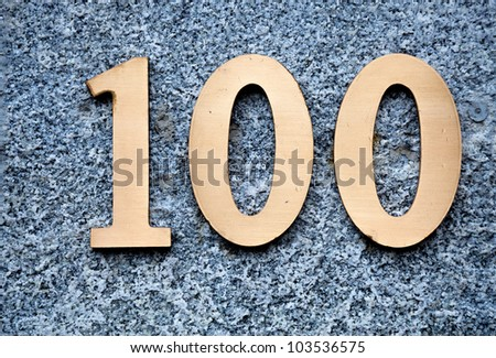 number 100 on the wall of a building - stock photo