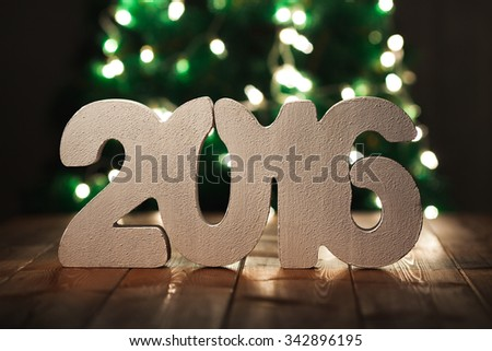 number 2016 on wooden table background, new year template, with fir tree out of focus on background - stock photo