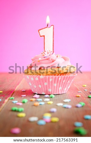 Number one birthday candle on a pink cupcake on a wooden table - stock photo