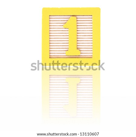 number one in an alphabet wood block on a reflective surface - stock photo